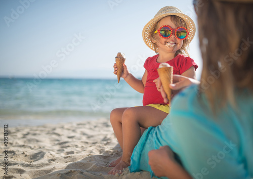 Mother and doughter eating ice cream on sandy beach