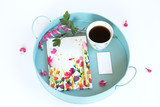 Notes in flowers, business cards with a cup of coffee and flowers on a tray. White background.