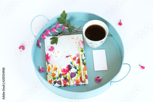 Poster Notes in flowers, business cards with a cup of coffee and flowers on a tray. White background.