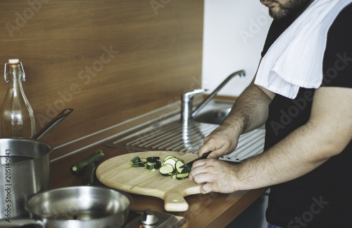 a man cooking at home, chopping vegetables, preparing healthy meal. Lifestyle, clean eating, vegan, detox, dieting food concept