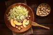 Frischer Salat aus Eisbergsalat, Nektarinen und Gurken mit Croutons auf Holzbrett, fotografiert mit natürlichem Licht