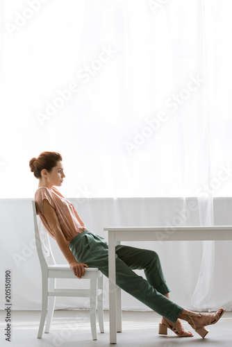 side view of beautiful young woman sitting at table at home