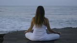 Rear view of mindful woman sitting in lotus pose on coastline and meditating while listening to ocean - 205153513