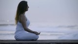 Side view of calm woman in white sitting in lotus pose and meditating near ocean - 205153556