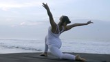 Medium shot of mindful woman in white doing low lunge yoga pose on coastline - 205153702