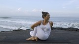Mature flexible woman practicing yoga on coastline: she doing seated twist pose, then raising leg and holding it - 205154738