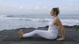 Side view of mature woman in white practicing yoga on coastline: she doing reverse plank pose, then transitioning into seated twist position - 205155582