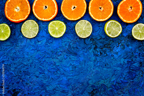 Oranges and lime round slices pattern on blue background top view copy space