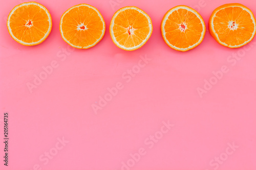 Oranges round slices pattern on pink background top view copy space