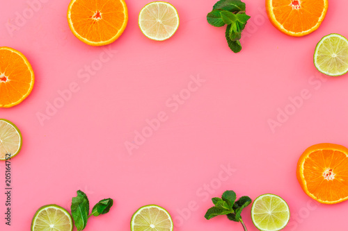 Oranges and lime round slices pattern on pink background top view copy space