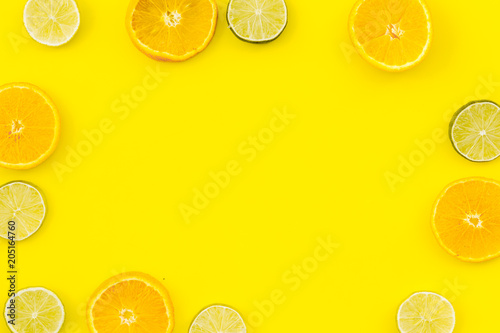 Oranges and lime round slices pattern on yellow background top view copy space