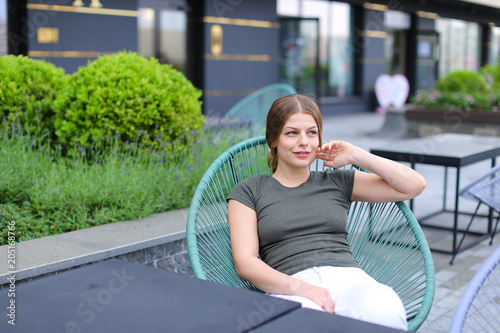 Poster Young woman resting at street cafe and sitting in chair near green plant. Concept of beauty and leisure time in open air.