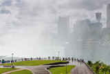 People walking in the fog on the observation deck next to Niagara Falls with the city on Background in USA