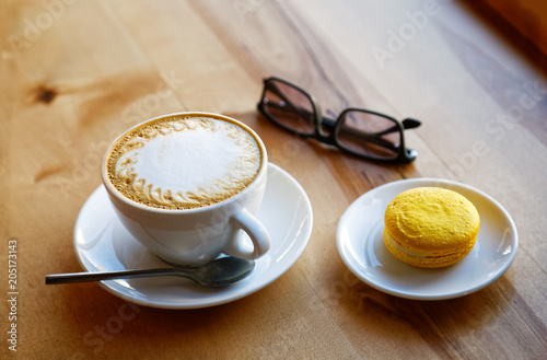 Poster White cup of cappuccino and saucer with yellow macaroon cookie on wooden table