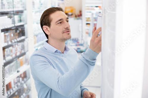 Fotobehang Apotheek I take this. Top view of appealing handsome man grabbing medication and reading