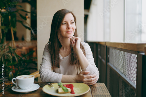 e952163c833 Attractive young woman sitting alone near big window in coffee shop at  table with cup of ...