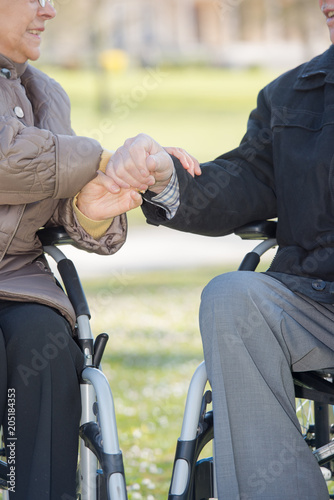 Closeup of hands of elderly couple in wheelchairs