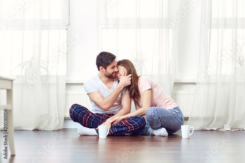 A loving couple hugging on the floor against the window in the room.