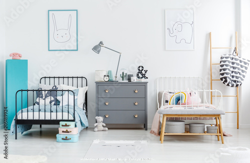Grey cabinet with lamp between black and white bed in siblings bedroom interior with posters. Real photo