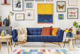 Navy blue couch with bright blanket and two cushions standing in white living room interior with fresh flowers, gold lamp and gallery on the wall