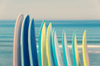 Stack of colorful surfboads on ocean background with waves, retro vintage filter