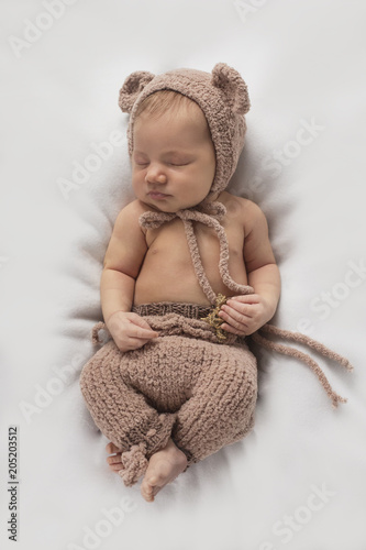 Newborn baby sleeps in a bear costume