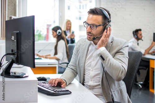 Technical support operator with hands-free headset talking with customer in call center.