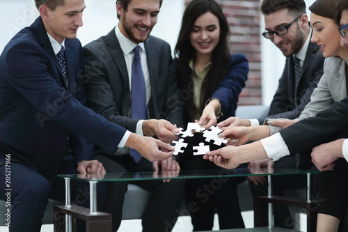 Business team solving puzzle together. - 205217966