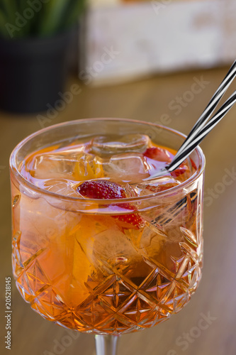 Cocktail with vodka, strawberries and lemon in glass on the bar