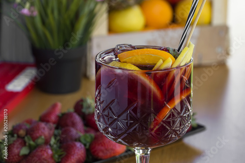 Cocktail with vodka, strawberries and lemon in glass