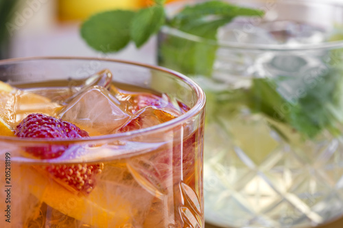 Two cocktails with vodka, strawberries, mint and lemon in glasses