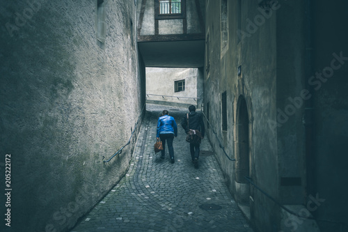 Canvas Smalle straatjes Geneva, Switzerland - May 13, 2018 : a men and a women travels the steep streets of Geneva's Old Town