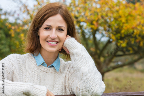 Foto Murales Attractive Happy Middle Aged Woman Resting on Fence