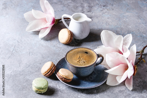 Sticker Blue cup of black espresso coffee with french dessert macaroons, cream and spring flowers magnolia branches over grey texture background. Top view, space.