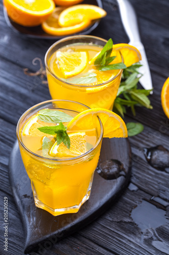 orange cocktail with ice and fresh mint on a black wooden table