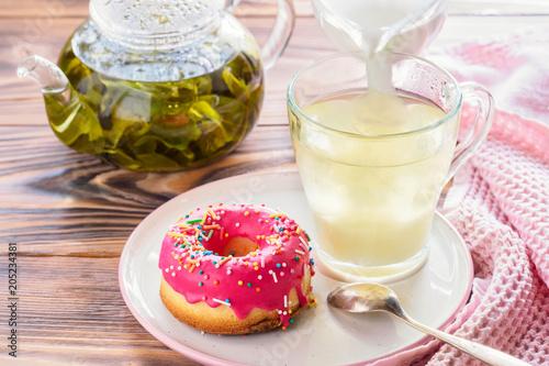 Kubek gorących naparów zielonej herbaty z pączkami glazurowanymi