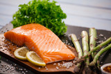 Fresh raw salmon fish served on black stone on wooden table - 205237118
