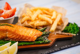 Fried salmon with french fries on wooden table - 205237153