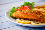 Fried salmon with french fries on wooden table - 205237168