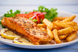 Fried salmon with french fries on wooden table - 205237172