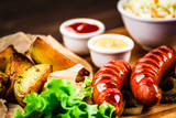 Grilled sausages, baked potatoes and vegetables - 205241745