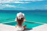 Carefree Woman relaxing in infinity swimming pool looking at view. Luxury resort. Beautiful destination summer vactions. Back view of traveller girl in beach hat and white bikini relax on Maldives. - 205247347