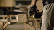 carpenter in the workshop saw a piece of wood with an electric chainsaw