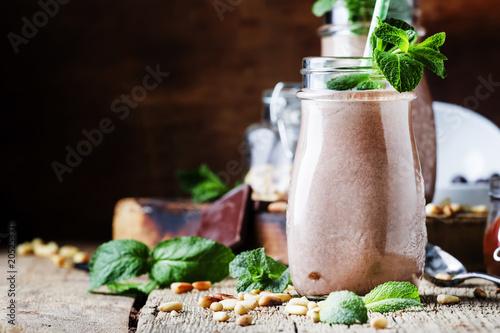 Plexiglas Milkshake Chocolate milkshake or cocktail with nuts and mint leaves, old wooden background, selective focus