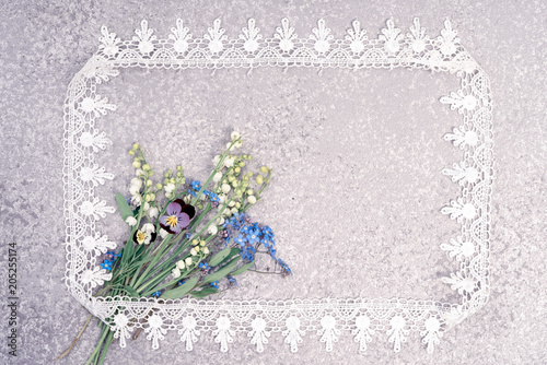 Aluminium Lelietjes van dalen lily of the valley, pansies and forget me not bouquet laying on an silver background in the lace frame with copy space for your greeting or invitation text. Holiday card.