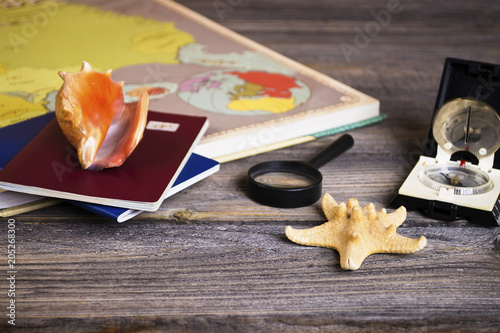 abstraction travel old compass, magnifier and passport on an old wooden background