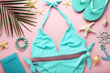 Blue swimsuit with palm leaf and starfishes on pink background - 205270396