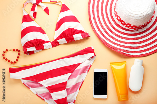 Striped swimsuit with hat and cosmetic bottles on orange background