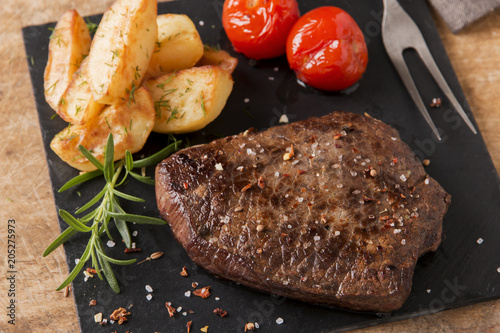 Plexiglas Steakhouse cooked beef steak with fried potatoes and tomatoes