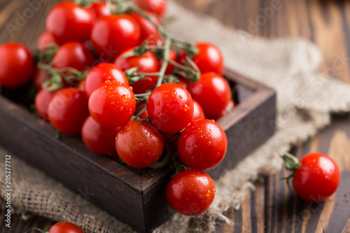 Plexiglas Kersen Small red cherry tomatoes on rustic background. Cherry tomatoes on the vine
